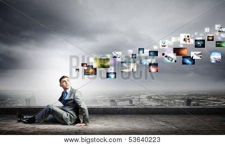 Image of young man sitting on floor looking on media icons