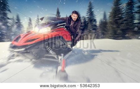 young man driving  snowmobile at beautiful winter day - in motion