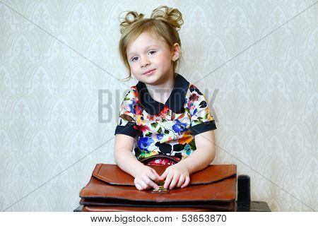 A little girl with a large portfolio