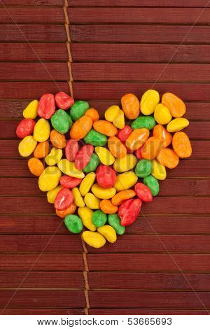Colorful dragees of peanuts arranged in a shape of heart poster