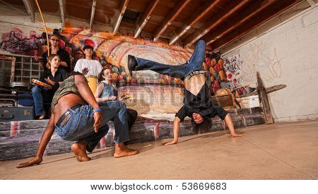 Group of capoeira performers in urban building doing flips poster
