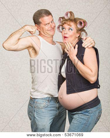Man Showing Biceps To Pregnant Woman