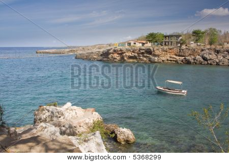 Small Boat Anchored In A Bay