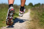 Trail running. Freeze action closeup of running shoes in action. Shallow depth of field focus on left shoe. poster
