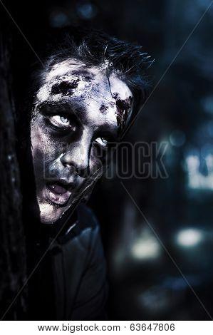 Head Of A Scary Zombie Peeking From Behind Tree
