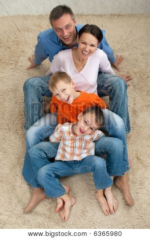 Family Of Four Sitting On The Carpet