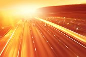 Cars in motion blur on highway during sunset. poster
