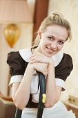 Hotel service. Portrait of female housekeeping or housemaid with vacuum cleaner at inn room poster