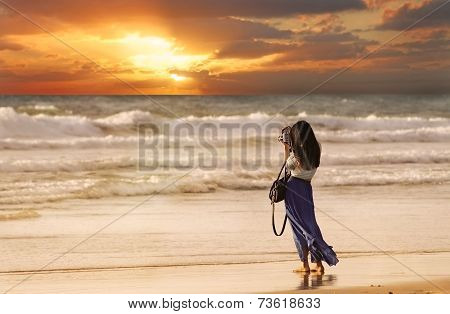Woman Taking a Picture on the Beach at Sunset