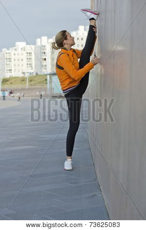 Flexible female athlete stretching her legs in a vertical split against a wall during the warming up before a training session