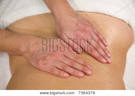 a closeup of a natural mature woman having a massage at her lumbar region poster
