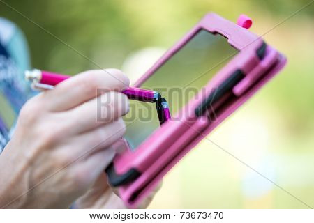 Woman Writing On A Tablet With A Stylus