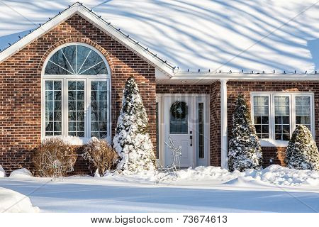 Brick detached home buried in snow and decorated for Christmas.