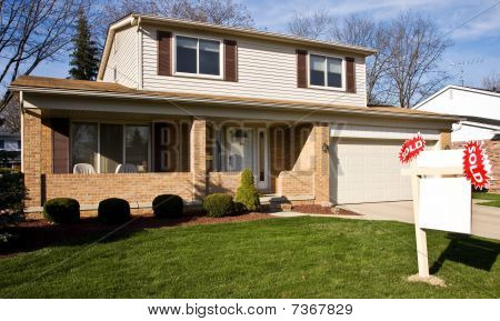 Real Estate Sold Sign In Front Of Residential Home