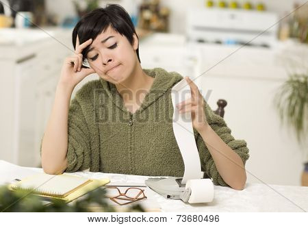 Multi-ethnic Young Woman Agonizing Over Financial Calculations in Her Kitchen.