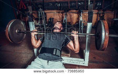 Young man lifting the barbell in the gym.