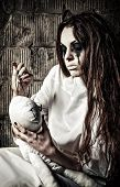 Horror scene: the strange crazy girl with moppet doll and needle in hands poster