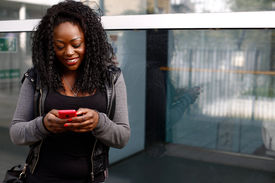 Young African Woman Sending An Sms On Her Mobile