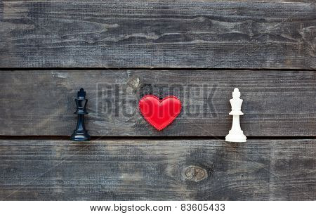 Red Heart Between Two Chess Kings On Rustic Wood