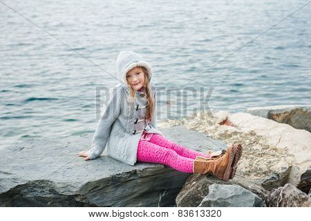 Pretty little girl resting by the lake