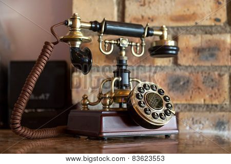 An antique analog telephone set with black box base and golden ringer and handset poster