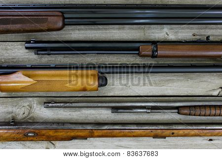 Collection of guns on rustic wood background