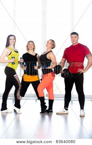 Group Of Positive Sporty Bodybuilders Doing Weight Training In Gym