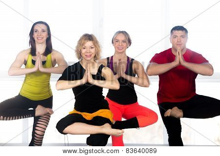 Group of four happy people enjoy fitness exercises in class standing in asana yoga pose in gym poster
