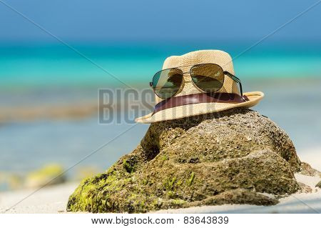 Straw hat towel beach sun glasses and flip flops on a tropical beach poster