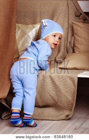 Little cute baby in pajamas, shot in home interior poster