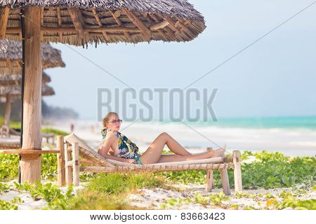 Woman sunbathing on tropical beach.