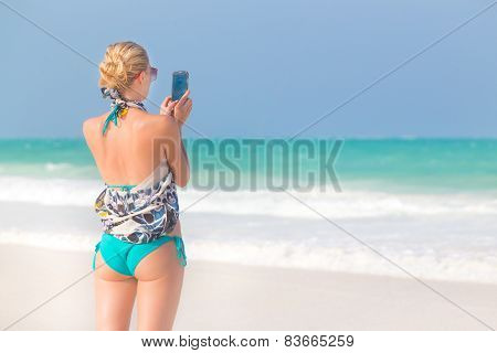Woman taking photo on the beach.
