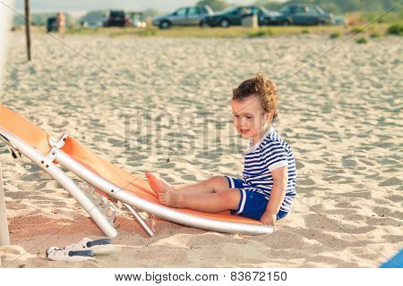 Playful Toddler Dressed As A Sailor Sitting On A Tilted Sunbed On A Beach. Photo With Untraditional