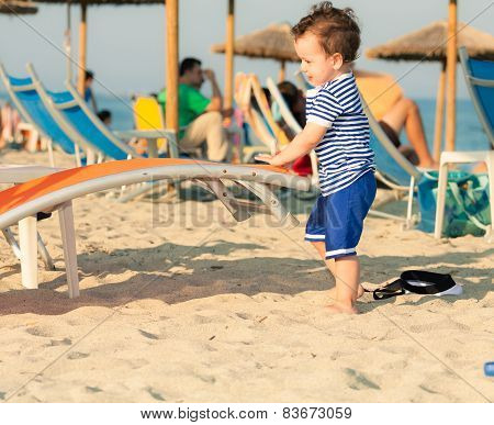Toddler Dressed As A Sailor Standing On A Beach And Playing With Sunbed With Other People In Defocus