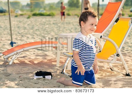 Toddler Dressed As A Sailor Standing On His Knees On A Beach And Giving A Playful Look. Photo With U