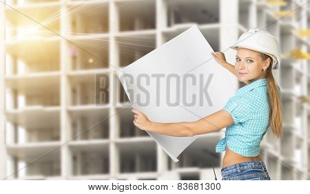 Woman holding blank drawing sheet in front of building under construction