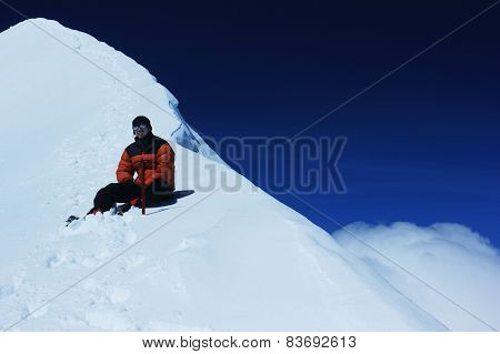 man sitting on a snowy slope in the mountains with ice axe