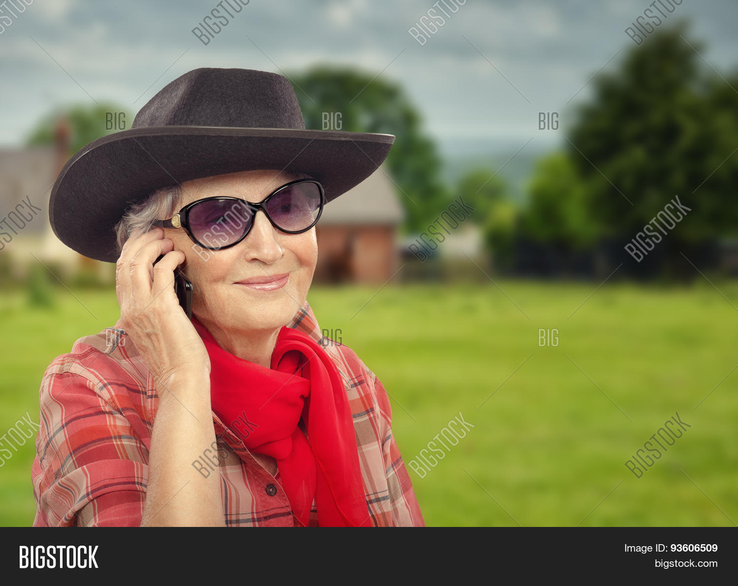 e84185fb80882 Old woman in sunglasses is wearing black cowboy hat and red plaid shirt.  Old cowgirl in red neckerchief is posing on countryside background out ...