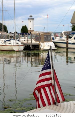 American Flag In Harbor With Boats And Lighthouse