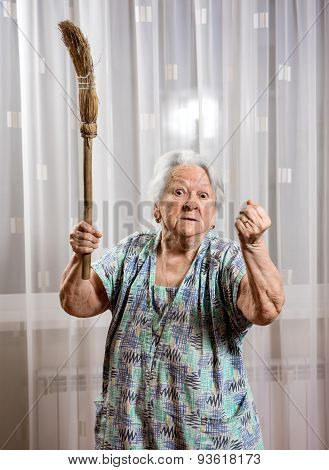 Old Angry Woman Threatening With A Broom