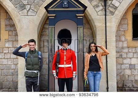 WINDSOR, ENGLAND - JUNE 11, 2015: Young couple posing with a beefeater guard at Windsor Castle, Berkshire, UK smiling and saluting the camera on June 11, 2015