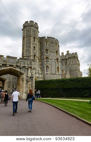 WINDSOR, ENGLAND - JUNE 11, 2015: Crenelated fortified medieval towers and stone archway at Windsor Castle, Berkshire, UK with sightseeing tourists walking on the path on June 11, 2015