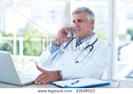 Smiling doctor having phone call at his desk in medical office