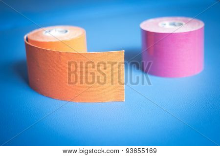 Physiotape physiotherapy color tape bandage kinesiotape rolls for kinesiotaping taping treatment in real life hospital clinic. poster