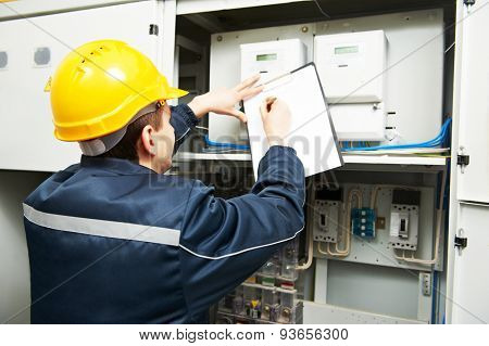 electrician builder engineer inspector checking data of equipment in fuse box