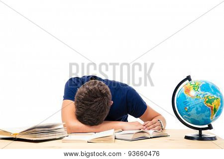 Tired male student sleeping on the table with books and globe isolated on a white background
