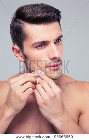 Man cleaning face skin with batting cotton pads over gray background
