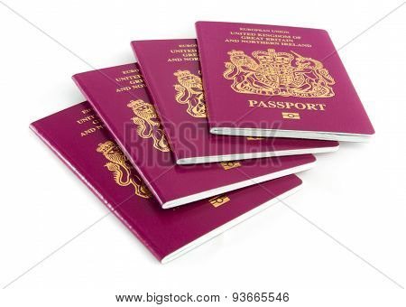 Four British Passports on a White Background