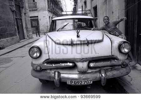 Boy and a classic American car in Havana