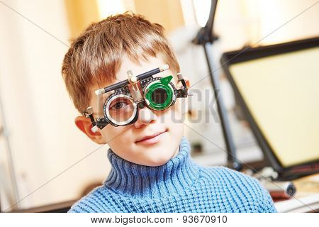 ophthalmology concept. young boy with phoropter during sight testing or eye examinations in clinic